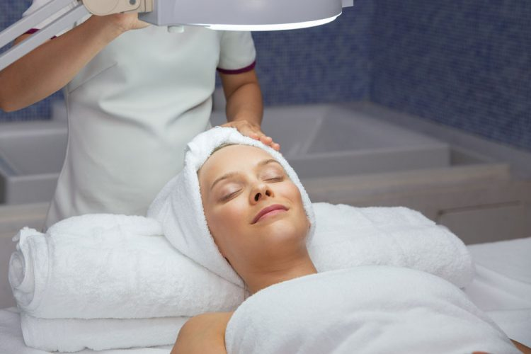 Portrait of happy young Caucasian woman lying on massage table, keeping her eyes closed, relaxing after facial treatment in spa salon